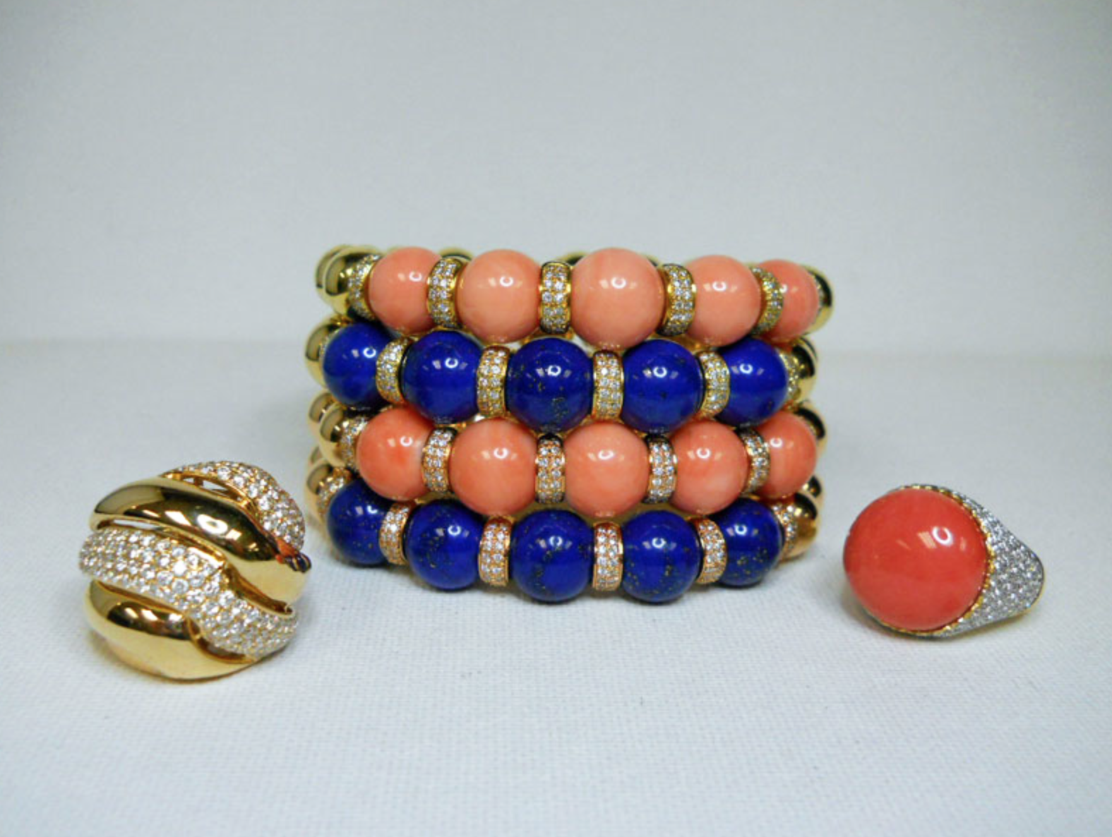 Alexia Echevarria pairs these colorful Coral, Lapis, Diamond & Yellow Gold stacked cuffs and Coral ring with a navy blue wrap dress for a fashionable day at the office.